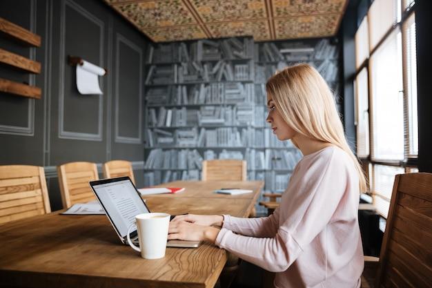 Невероятная молодая женщина сидит возле кофе во время работы