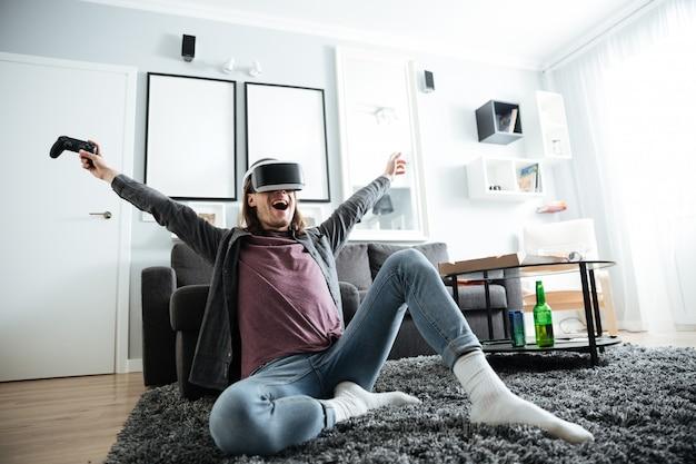 Веселый человек сидит дома в помещении играть в игры