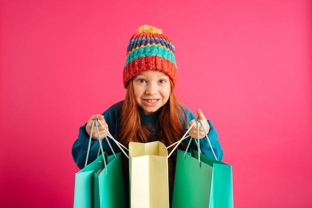 幸せな美しい女の子の買い物袋を押しながら分離カメラを探して