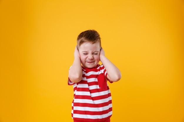 耳を覆う怒っている不幸なイライラした小さな男の子の肖像画