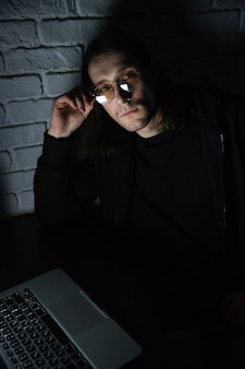 Сконцентрированный человек используя портативный компьютер дома