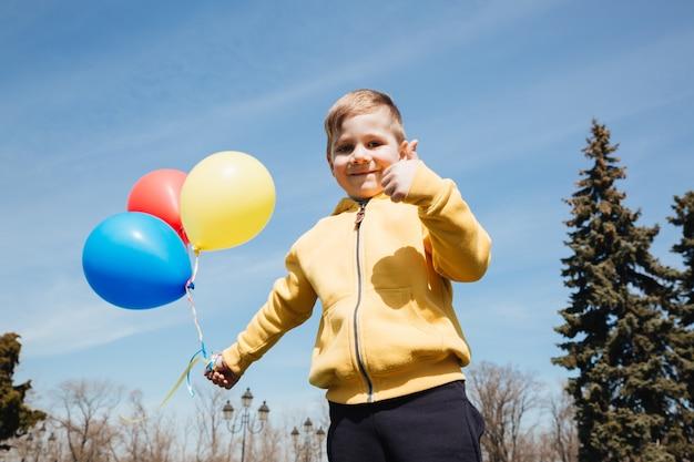 Улыбающийся маленький ребенок мальчик с воздушными шарами.