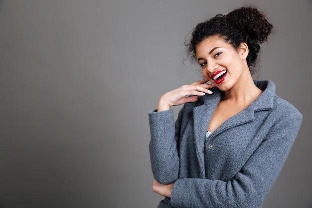 Портрет улыбающейся молодой женщины в пальто
