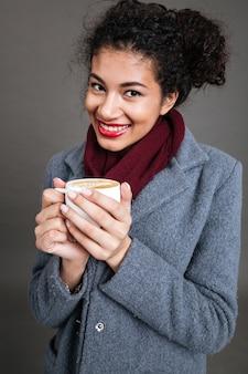 Улыбается счастливая женщина в пальто, держа чашку кофе