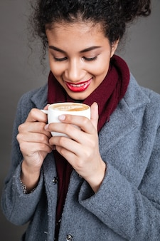 一杯のコーヒーを保持しているコートで笑顔の幸せな女