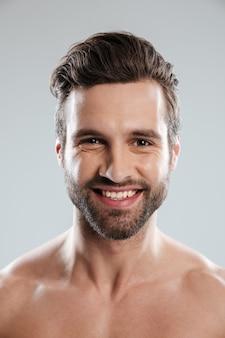 Крупным планом портрет улыбающегося молодого бородатого мужчины