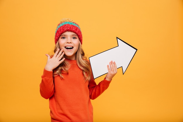 セーターと帽子の紙の矢印を指すとオレンジ色でカメラを見て幸せな若い女の子
