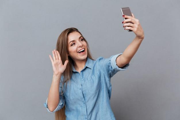 Счастливая женщина в рубашке делает селфи на смартфоне