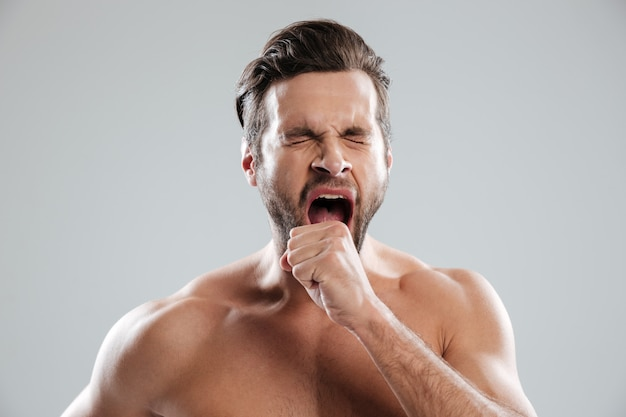 Портрет скучающего бородатого мужчины с обнаженными плечами зевая