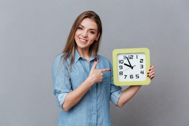 時計を保持しているシャツの女性の笑みを浮かべてください。