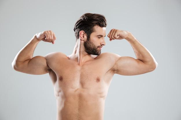 彼の上腕二頭筋を示す自信を持って男性