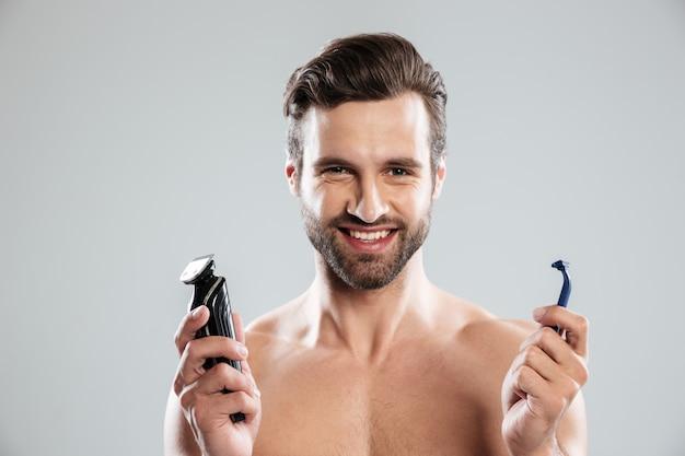 Счастливый молодой человек, выбирая бритву
