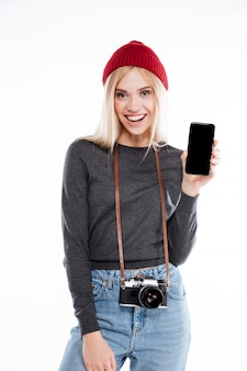 携帯電話を示す笑顔金髪の若い女性写真家の肖像画