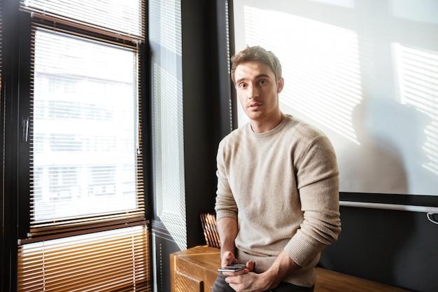 Привлекательный молодой человек в офисе, глядя и с помощью телефона