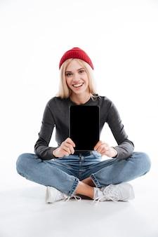 Женщина сидит на полу и показывает пустой экран планшета