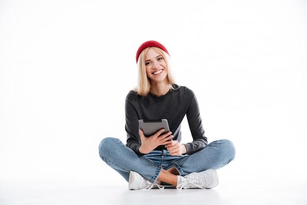 Улыбается женщина, сидя на полу и с помощью планшетного компьютера