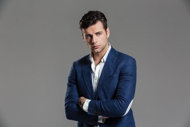 Портрет серьезного сосредоточенного мужчины в куртке позирует