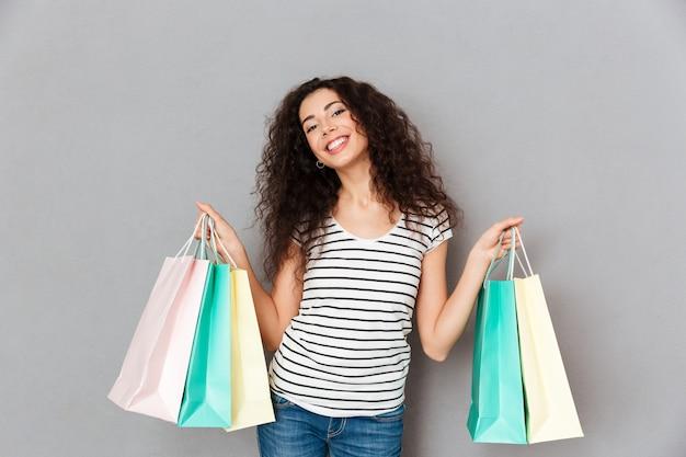 に笑みを浮かべて灰色の壁に立っている間購入を示す多くのパッケージとカメラでポーズトレンディなファッション女性の肖像