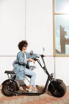 現代のバイクに座っているスタイリッシュな若い女性