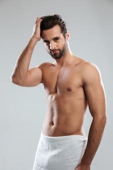 Концентрированный молодой человек, одетый в полотенце