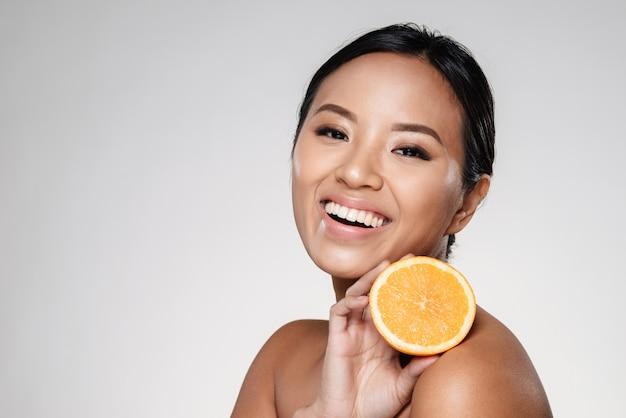 Женщина держит апельсиновые дольки возле ее лица