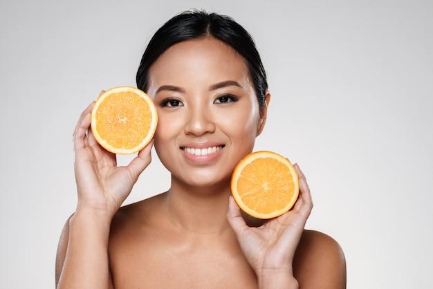 彼女の顔の近くのオレンジスライスを保持している女性