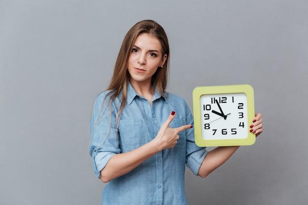 時計を保持しているシャツの深刻な女性