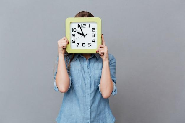 時計の後ろに隠れているシャツの若い女性