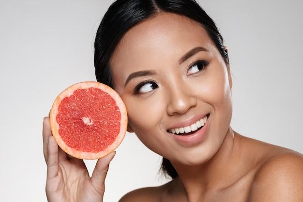 Красивая азиатская дама смотрит в сторону и держит кусочек грейпфрута возле лица