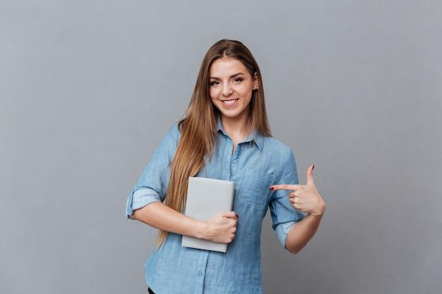 本を手に持ったシャツの女性