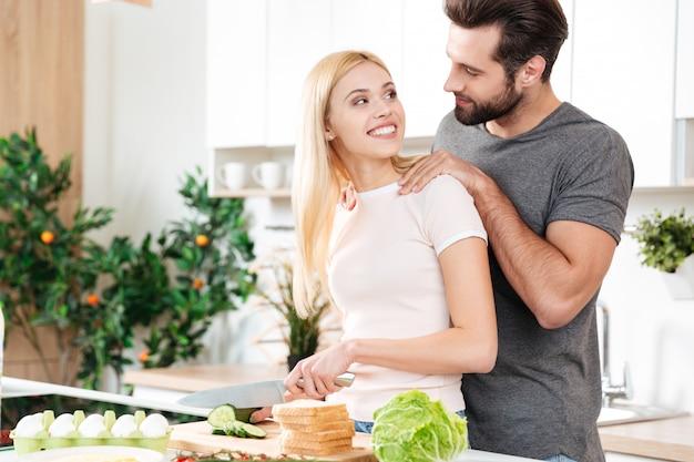 Счастливые молодые влюбленные стоя на кухне и приготовления пищи