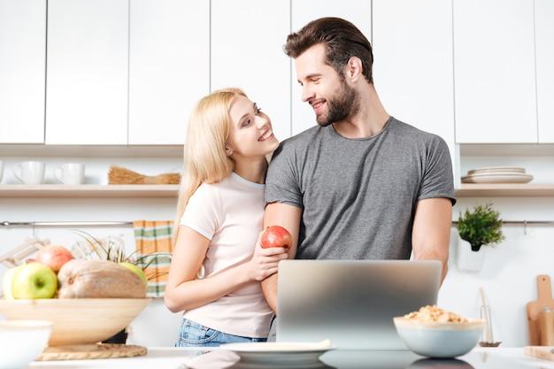 ラップトップコンピューターとキッチンで料理をしてカップル