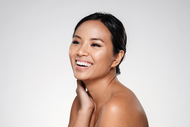 Красивая улыбающаяся азиатская леди смотрит в сторону