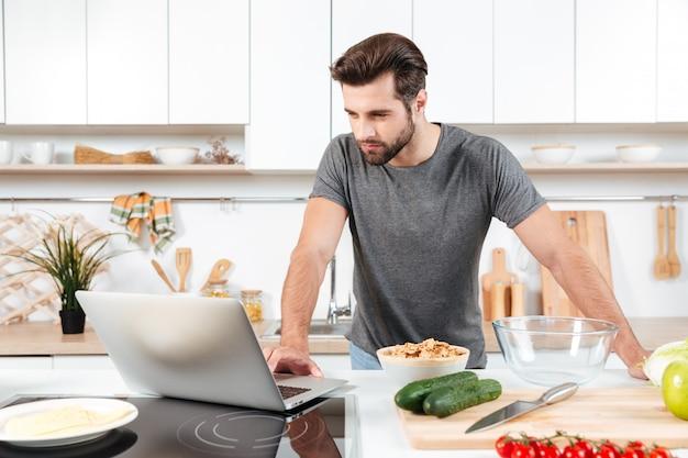 Мужчина ищет рецепт на ноутбуке в кухне дома