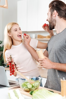 Молодой улыбающийся мужчина и женщина на кухне, приготовление пищи с ноутбуком