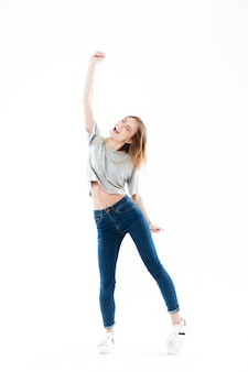 Портрет жизнерадостной счастливой молодой женщины празднуя успех