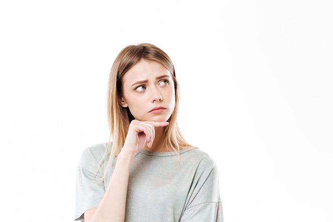 Унылая думая молодая женщина стоя изолированный