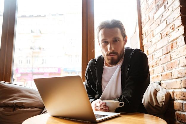 Серьезный бородатый мужчина в кафе у окна