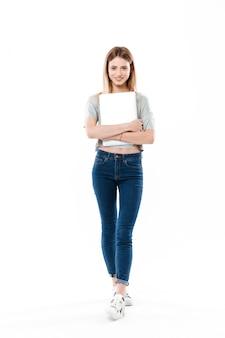 Молодая женщина, держащая портативный компьютер