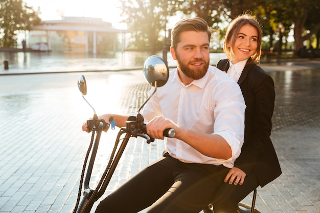 Вид сбоку улыбается пара бизнес едет на современном мотоцикле