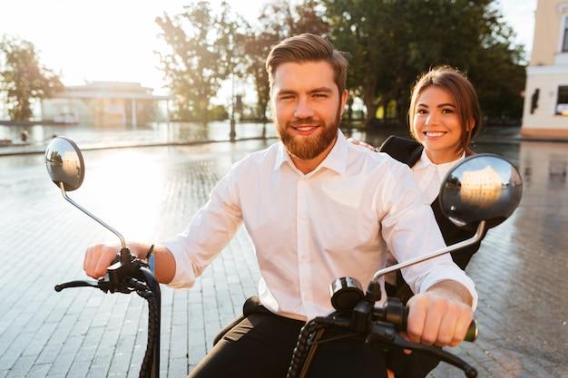 Улыбаясь бизнес пара едет на современном мотоцикле на открытом воздухе