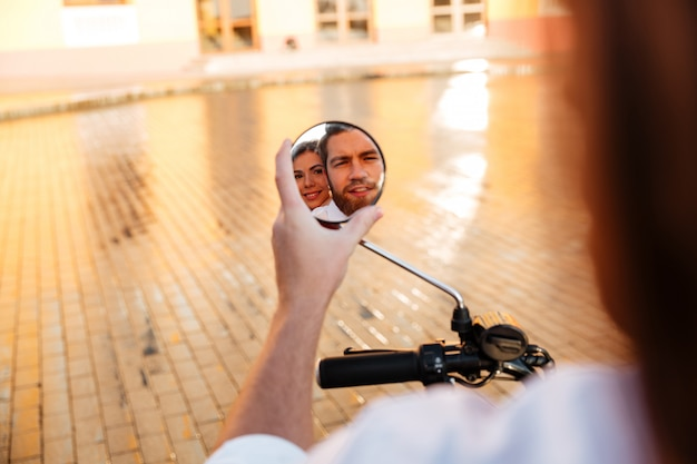 Изображение деловой пары едет на современном мотоцикле на открытом воздухе