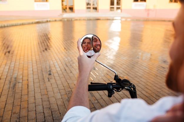 Изображение улыбающегося бизнес пара едет на современном мотоцикле