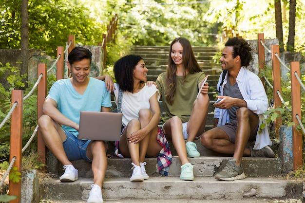 Многонациональные друзья студенты на улице с помощью мобильного телефона и ноутбука