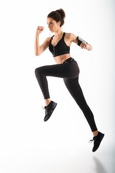 Концентрированная кудрявая брюнетка фитнес женщина работает и слушать музыку