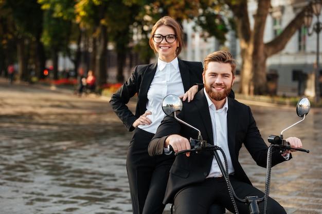 Улыбаясь бизнес пара позирует с современным мотоциклом на открытом воздухе