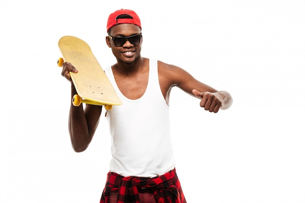 Улыбающийся молодой человек, держа скейтборд и показывает палец вверх