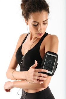 音楽を聴くと、スマートフォンを使用して若いカーリーブルネットフィットネス女性
