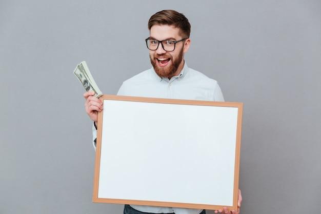 Счастливый молодой бизнесмен держит пустую доску и деньги