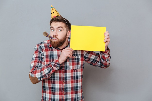 空白のボードを持ってハンサムな若いひげを生やした誕生日男